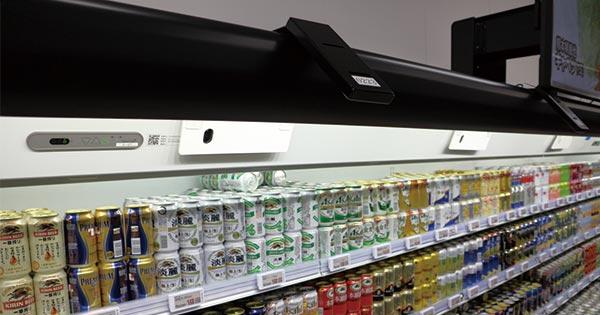 棚の上部にある白いカメラが客を認識し、その上の黒いカメラが棚の動きを認識する。客に合わせたサイネージ