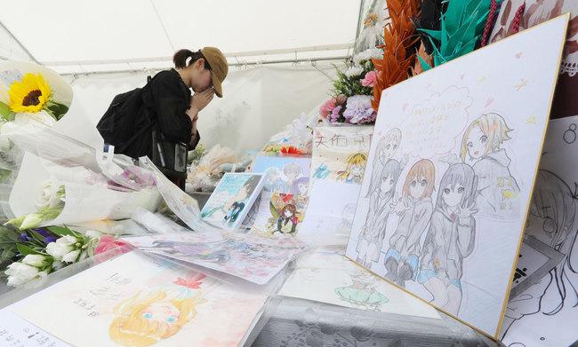 「京都アニメーション」第1スタジオ近くに設けられた献花台で手を合わせる女性(8月18日、京都市伏見区)