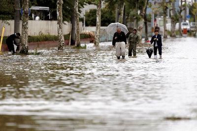 福島県郡山市の郡山中央工業団地で冠水した道を歩く人たち