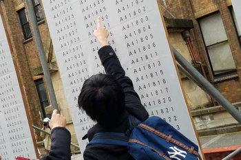 東大の合格発表の日、自分の受験番号を見つけた黄さんの子ども
