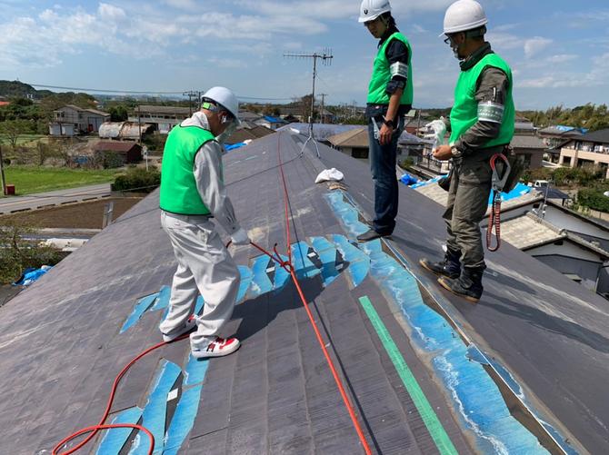台風で被災した家の屋根にブルーシートを張る職人たち(提供:ユニオンテック)