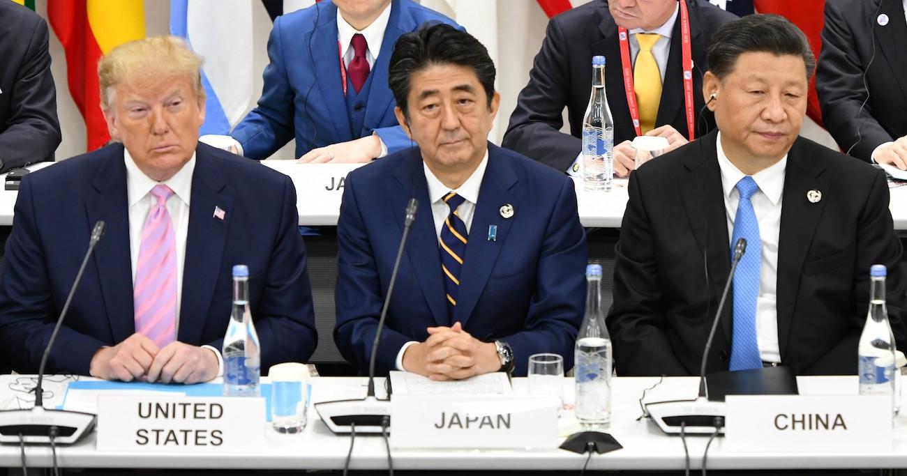 デジタル経済をテーマとした会合で肩を並べる米国のトランプ大統領(左)、安倍晋三首相(中央)、中国の習