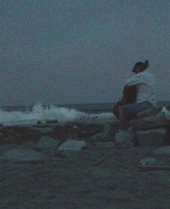 日が暮れた浜辺で、壊れた堤防の破片に腰かけ、演奏する英順さん