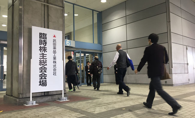 武田薬品工業の臨時株主総会。「買収完了で完全に外資系製薬会社となる」と買収反対派の株主はぼやいた